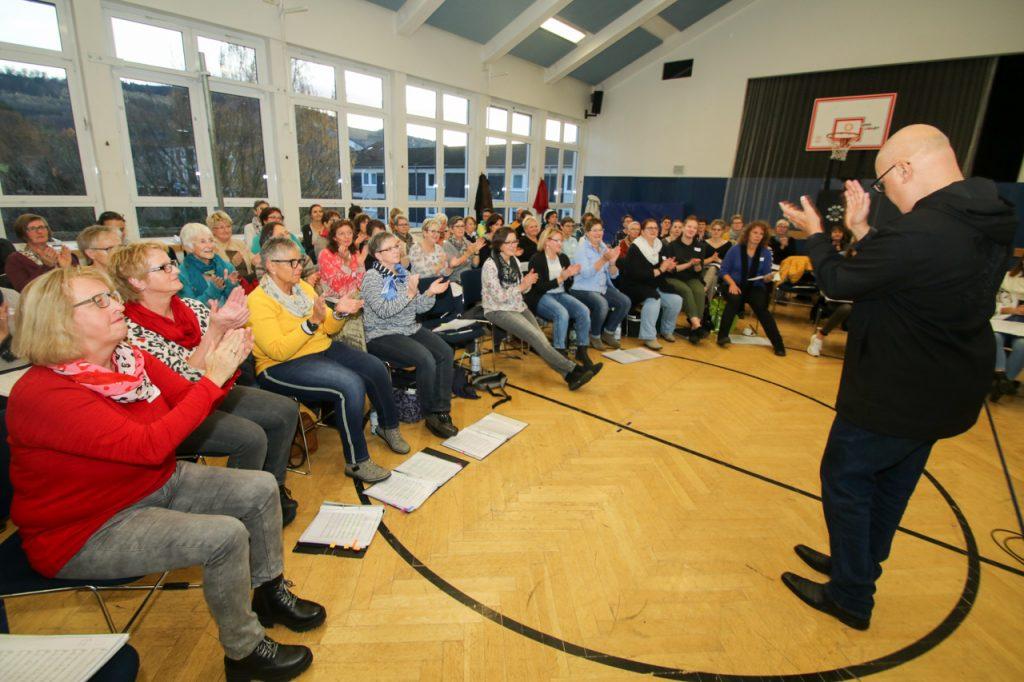 """Immer wieder bittet Carlos die 100 Sängerinnen und Sänger, die Noten aus der Hand zu legen. Entscheidend ist das """"Gefuuuhl"""". Foto: Kultur Pur/Ulrich Bock"""